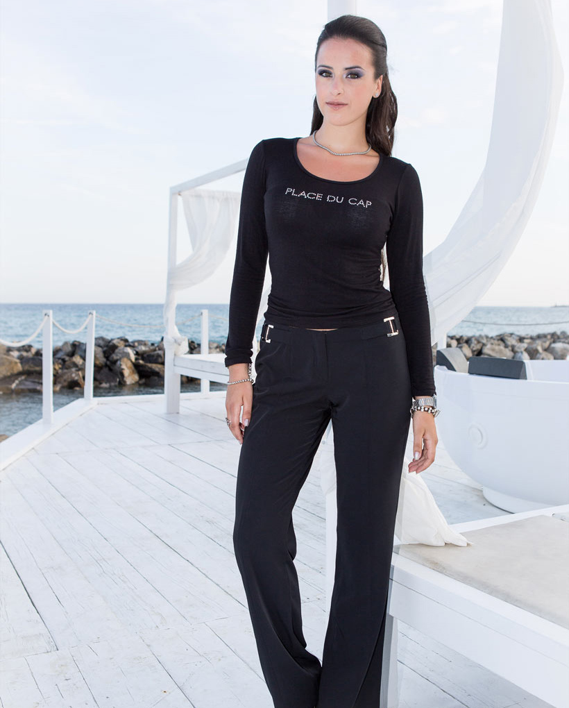 Black long trousers with silver coloured metal buckles at the waistline